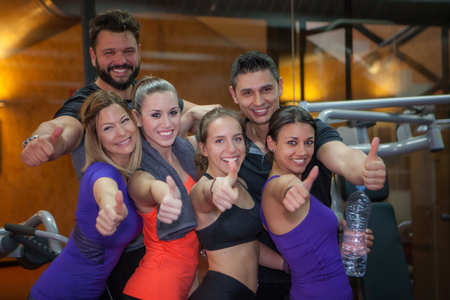 group of fit people at gym thumbs up Stockfoto
