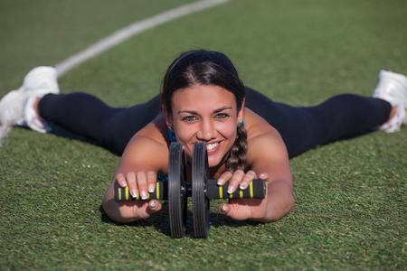 female fitness: fitness female athlete exercising with toning wheel Stock Photo