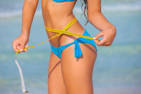 summer diet: slim woman in bikini with tape measure for summer diet concept. Stock Photo
