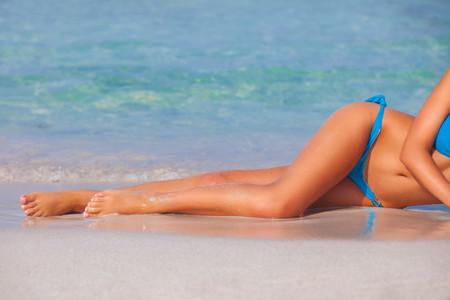 sea beach: woman sunbathing on beach on summer vacation in Spain Stock Photo