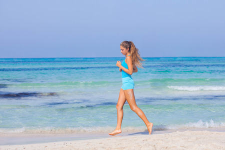 healthy woman running or jogging  on beach