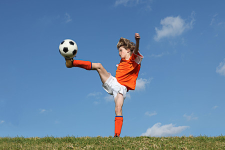 kid playing football or soccer kicking ball photo