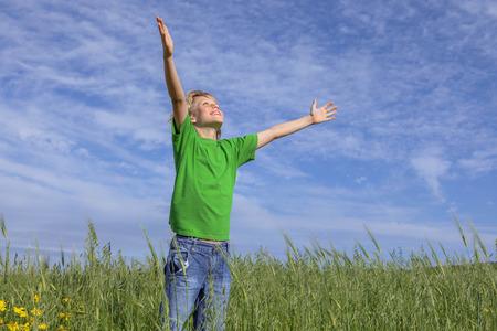 faith happy christian boy arms raised in prayer. photo
