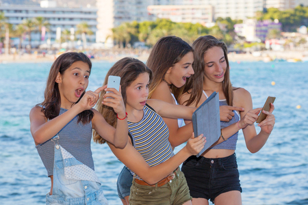 Children playing with   App game on mobile phones and   on vacation on the beach in Mallorca Spain. Redactioneel