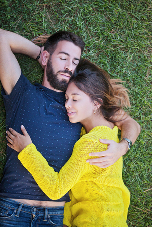happy couple in love laying on grass in summer