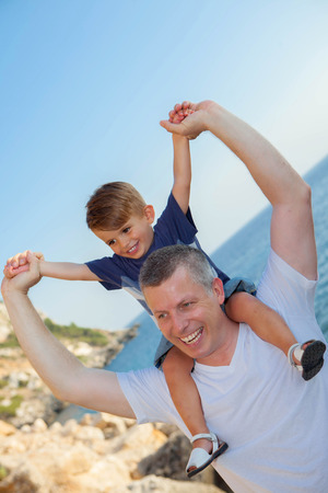 father and son piggyback on summer holiday vacation