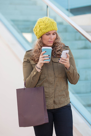 woman shopping with coffee and mobile or cell phone Stockfoto
