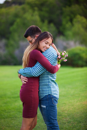 valentines couple hugging with gift of flowers,