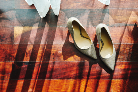 The sun light through curtain, the glittering shoes with shadow on the wooden floor 스톡 콘텐츠