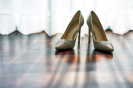 The women's shoes on the wooden floor with shadow on the floor, the sun light behind the white curtain - low angle