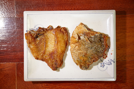 2 of tilapia fish fried on plate on wooden floor - top view, close up
