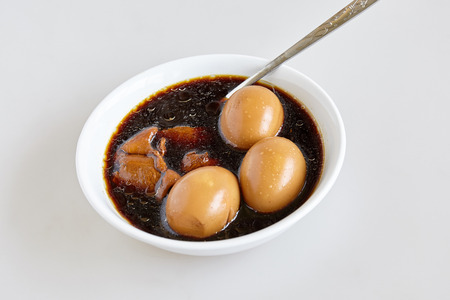 The hard-boiled eggs and pork and tofu in the sweet brown gravy sauce on the white background (Thai's named Kai-Pa-Lo)- top view