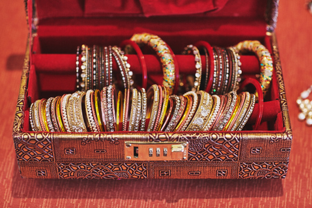A collection of glitter and shiny bracelets or bangle in various jewely decoration in the luxury red box for indian bride