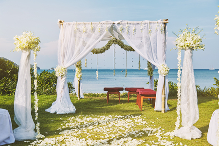 The beautiful wedding venue setting with flowers, floral decoration on arch with panoramic ocean view in background Stock Photo