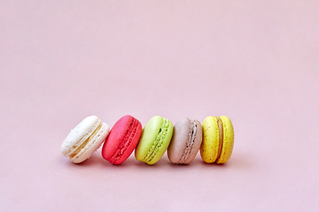 A group of colorful french dessert macaroons or macaroons arrange on the lemonade color background with space for text, isolated on a pink background Stockfoto