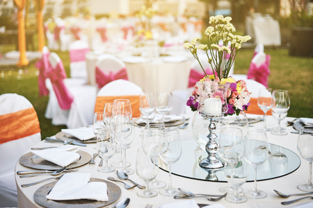 Wedding reception dinner table setting with empty glasses of water, wine and dinner wear with flower decoration, and white fabric cover chairs with pink sash