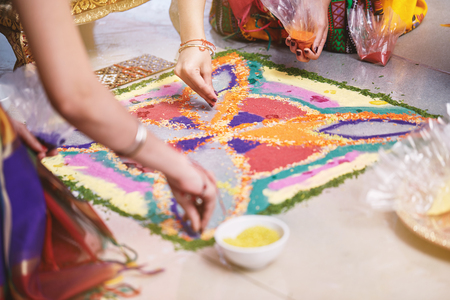 Women helps coloring tradition colorful rice art or sand art (Rangoli) on the floor with paper pattern using dry rice and dry flour with colored from natural pigments like sindoor, haldi (turmeric) Stock Photo
