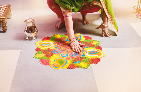 Women coloring tradition colorful rice art or sand art (Rangoli) on the floor with paper pattern using dry rice and dry flour with colored from natural pigments like sindoor, haldi (turmeric) Stockfoto