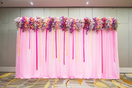 The beautiful backdrop with pink fabric decoration with various color of flower and ribbon for the wedding reception