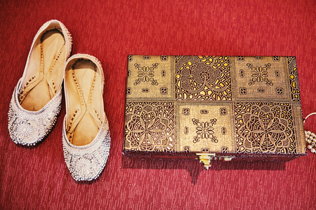 A pair of white pump shoes and red box of bangles (bracelets) of an Indian bride on red background