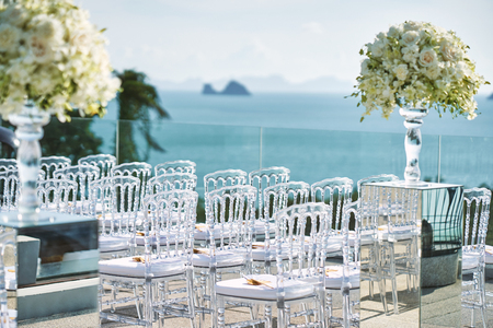 White flower and roses bouquet decoration with the transparent vase on the mirror box with transparent ghost chairs line up, panoramic ocean view Stock fotó
