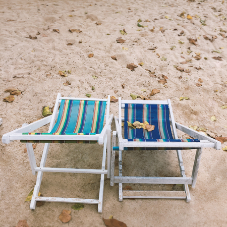 Two empty deck chairs with blue and green stripes for relazation on the beach, Summer holiday concept