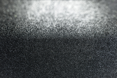 Black glitter background with selective focus on surface texture with defocused area in background