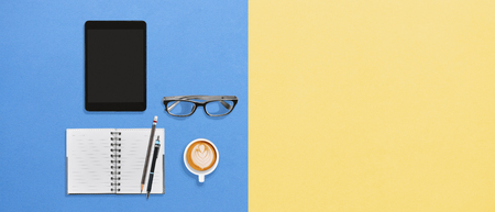 Modern office desktop flat lay working space lifestyle with tablet, notebook, pens, eyeglasses and a cup of hot coffee frothy drink on creativity color yellow blue background with copy space