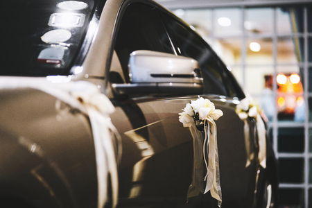 White ribbon and flower decorating at the car door and trunk for newlyweds couple after wedding ceremony
