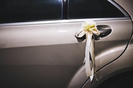 White ribbon and flower decorated on the car door of the wedding car for newlyweds