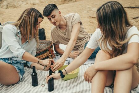 Group of young friends toasting with small bottles in a lake in the middle of the forest.