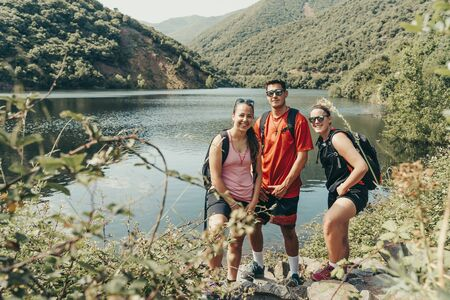 Young hikers in mountainous landscape with lake in summer. 版權商用圖片