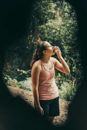 Girl eating an apple through a tree in nature. Foto de archivo