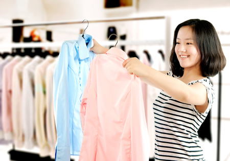 changing clothes: Woman shopping buying new dress in clothing shop choosing between two dresses.