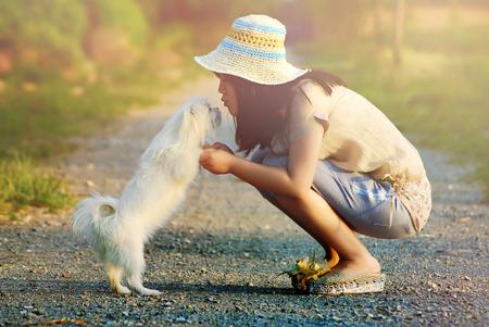 mujer con perro: Mujer feliz joven hermosa con el pelo largo y oscuro que sostiene el pequeño perro