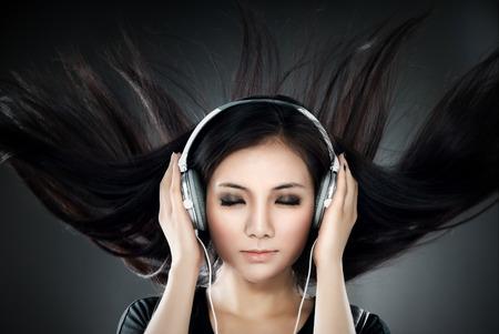 escuchando musica: Mujer escuchando música con el pelo que agita. Foto de archivo