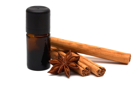 Essential oil with cinnamon sticks and anice on white  photo