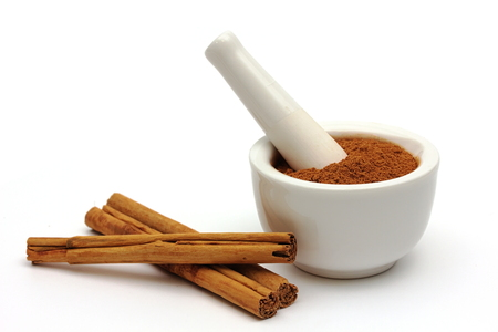 Ground cinnamon in a bowl with cinnamon sticks isolated on white  photo