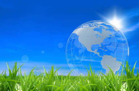 The globe in a green grass on a blue background