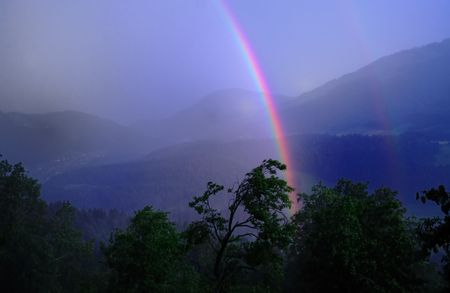 Rainbow on stormy day in the alps.