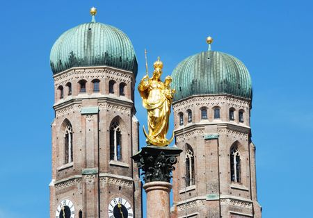 The golden sculpture of Saint Mary with the Church of Our Lady (Frauenkirche) in the background. View from the Marienplatz in Munich (Germany, Bavaria) Standard-Bild