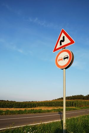 overtake: Landscape with a traffic sign: Dont overtake because of curves.