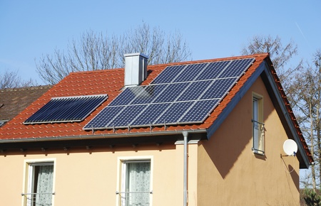 House roof with photovoltaics installation and solar heating system photo