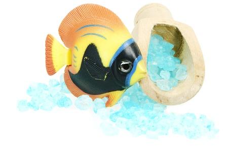 fish toy: Isolato sale da bagno blu in un cucchiaio woode e un pesce giocattolo