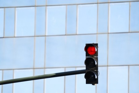red traffic light: Red traffic light in front of the glass facade of an office building