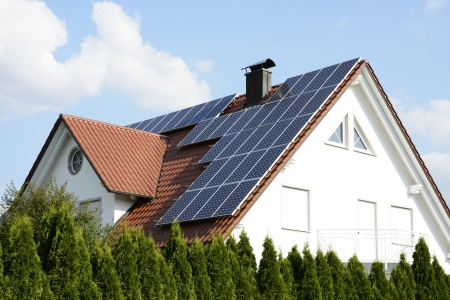 Green energy with solar panels on the roof of a modern house.
