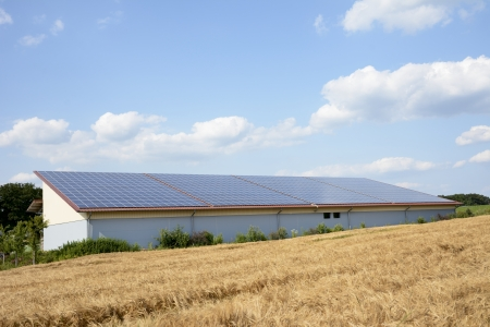 Barn at a wheat field with solar panels on the roof Stock Photo