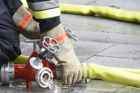 Hand eines Feuerwehrmannes Verbindung ein Feuerwehrschlauch mit einem Anschluss-Gerät. Standard-Bild - 22907657