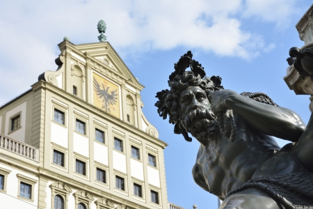 heads old building facade: The Augustus fountain (built 1594) in Augsburg with the town hall in the background. Stock Photo
