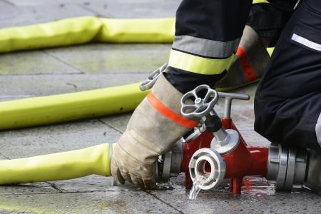 bombero de rojo: La mano de una conexi�n a una manguera de bombero a un dispositivo conector. Foto de archivo